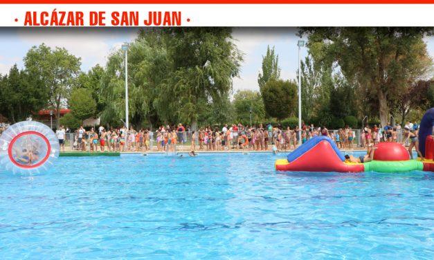 Cientos de niños disfrutan de una refrescante y divertida mañana con los hinchables de la piscina municipal en el Día del Agua