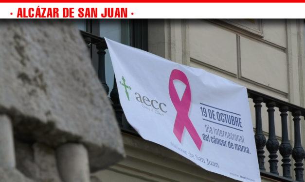 La banderola con el lazo rosa en apoyo a la lucha contra el cáncer preside la fachada del Ayuntamiento de Alcázar de San Juan que se suma al Día Mundial contra el cáncer de mama